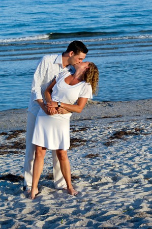 lovers kissing: A young couple a standing near beach kissing.