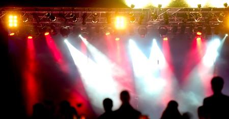 Multitud de personas delante de focos en un concierto.