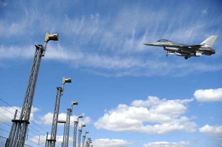 F-16 fighter plane is landing in airport. The sky is blue with white clouds photo