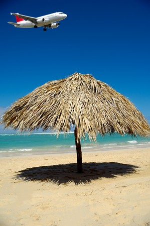 Parasol on beach and a plane is flying over it ready to land in airport. The plane is in blur. Stock Photo