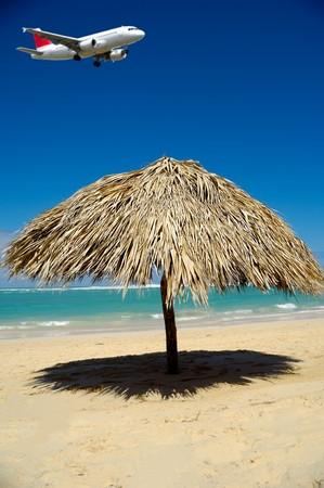 Sombrilla en la playa y un plano está volando sobre él listo para aterrizar en el aeropuerto. El avión se encuentra en el desenfoque.  Foto de archivo