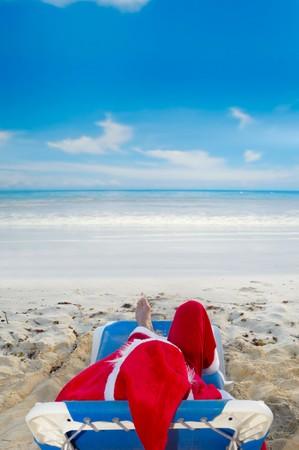 Santa claus está de vacaciones. Él está descansando sobre una silla sol en Playa exótico.