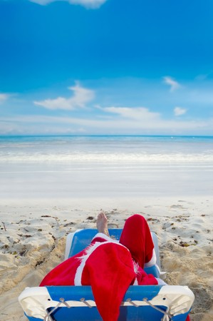 Santa claus is on vacation. He is resting on a sun lounger on exotic beach. Stock Photo
