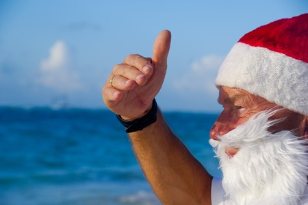 Santa claus is on vacation. He is looking at something on the beach. photo