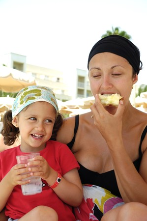 Healthy family. Mother and child eating apple and drinking water photo