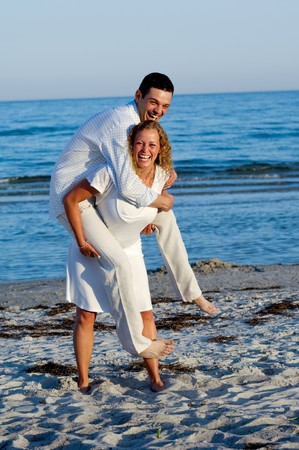A happy young woman and man having fun on beach.