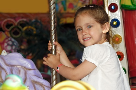 A sweet smiling child is sitting on horse in carousel photo
