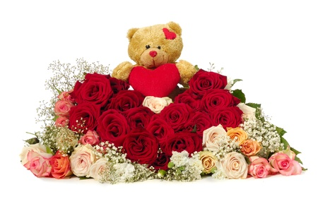 Bouquet of rose flowers isolated on white background. The roses are aranged as a heart shape. A teddy bear is sitting ontop of the flowers. photo