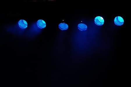 performace: Lights and smoke. Row of blue spotlights from a stage.