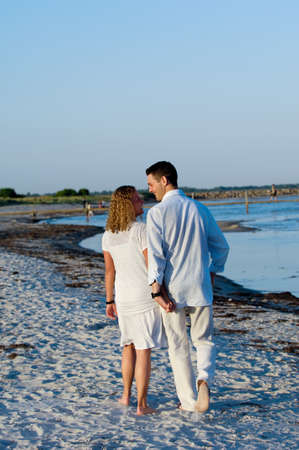 A young couple are walking on a beach. photo