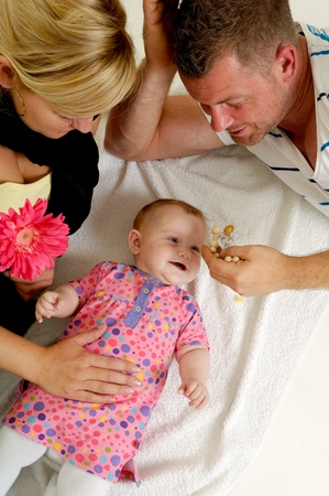 Mother and father are looking and playing with their sweet smiling 4 month old baby. photo