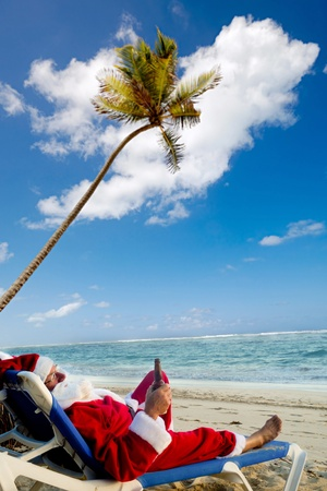 Santa claus is on vacation. He is resting on a sun lounger on exotic beach drinking a beer. Stock Photo
