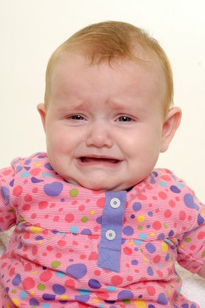 Sad baby is crying. Isolated on a white background. photo