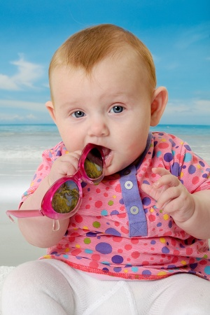 Sweet baby on vacation on beach with the sea in the background. Stock Photo - 10237990