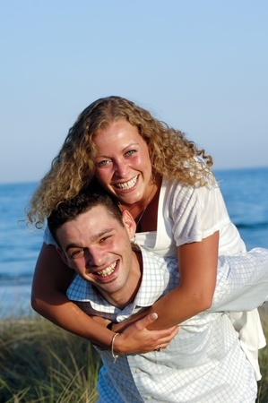 A happy woman and man in love at beach. The young man is carrying his girlfriend on the back of his shoulders. photo