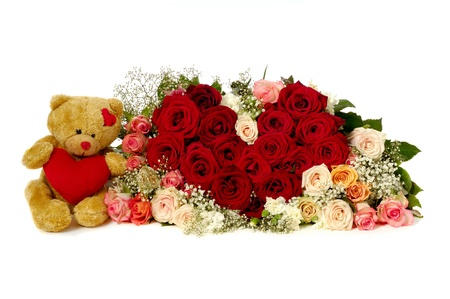 Bouquet of rose flowers isolated on white background. The roses are aranged as a heart shape. A teddy bear is sitting next to the heart. photo