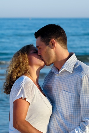 A young couple a standing near beach kissing.