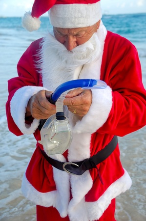 Santa claus is on vacation. He is getting ready to go and dive in the water. photo