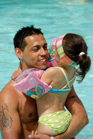 eachother: Father and daughter in pool giving eachother a hug