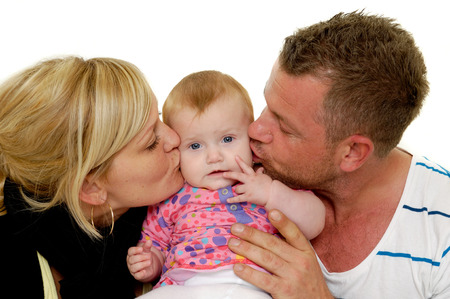 Mother and father are kissing their sweet baby 4 month old baby. photo