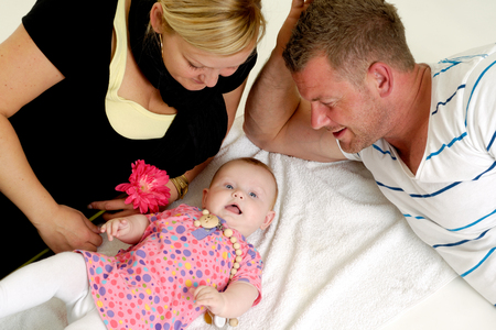 child in bed: Mother and father are looking at their sweet smiling 4 month old baby.