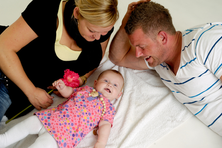 Mother and father are looking at their sweet smiling 4 month old baby. photo