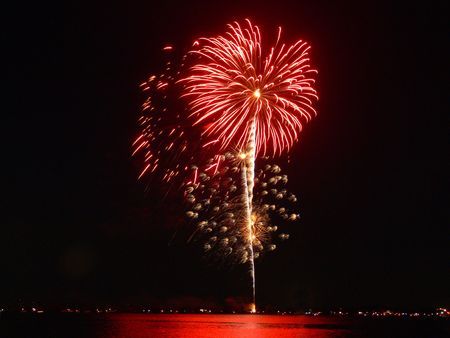 A photograph of a fireworks display near a lake.