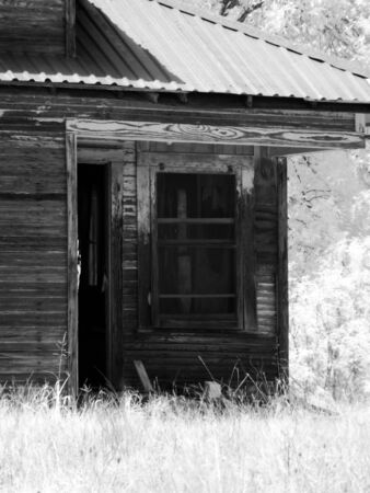 outbuilding: An infrared black and white photograph of the window and door of an old house.