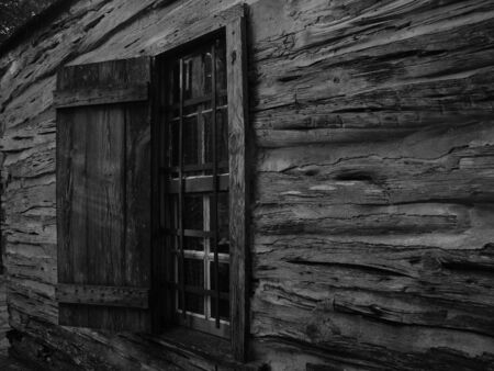 A black and white detail photograph of the logs and window of a log cabin. photo