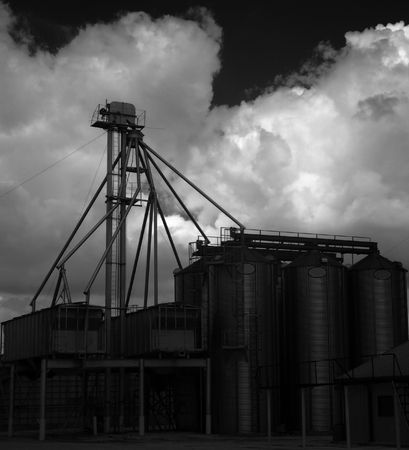 storage bin: A black and white infrared photograph of several metal grain silos with a stormy sky in the background.