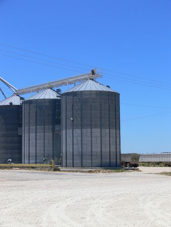 A photograph of several metal grain silos with a blue sky in the background. photo