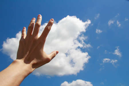 Hand stretched out to blue sky