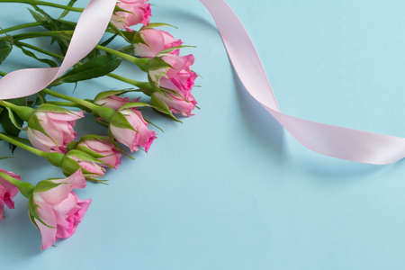Pink ribbon with a light blue background and an image of a rose gift Stock Photo