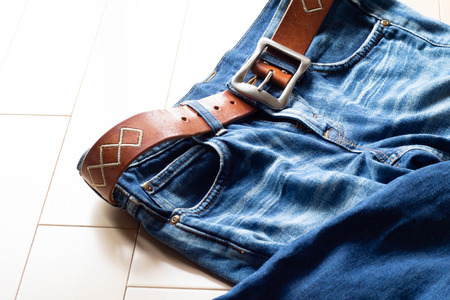 Bottoms of denim jeans and brown leather belt Stock Photo