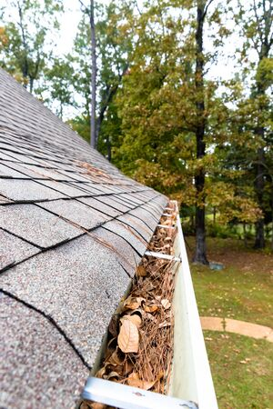 Leave and pinestraw filling gutters on home
