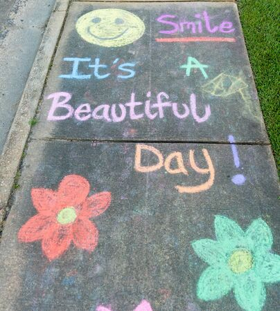 """the words """"Smile It's a Beautiful Day"""" written with sidewalk chalk on gray concrete pavement background"""