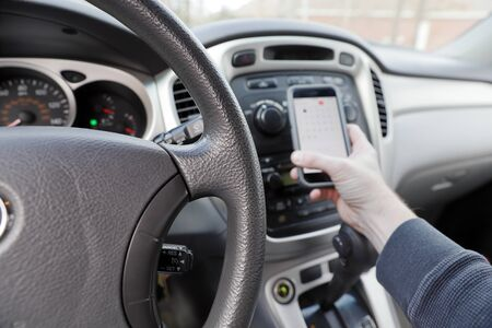 hand holding phone while driving, vehicle interior - shallow depth of field, abstract