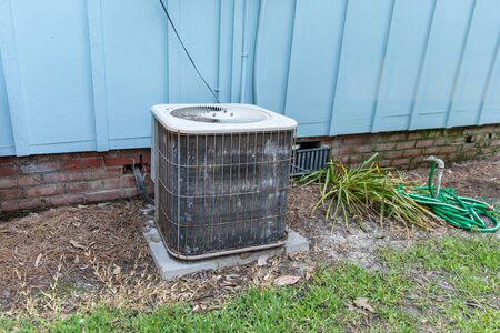Old air conditioner system compressor next to home, needing maintenance.