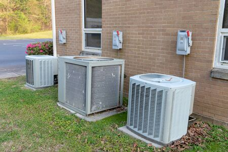 3 Air Conditioner Compressors outside commercial building with cutoff switches. Stockfoto