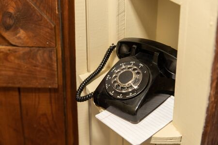 Old black rotary phone in hallway phone nook Stock Photo