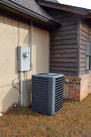 Gray Air Conditioner condenser compressor unit next to painted brick house. Zdjęcie Seryjne