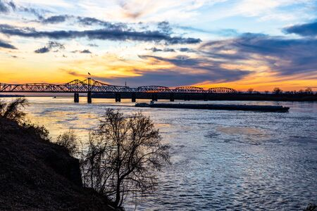 Sunset landscape of the Mississippi River bridge between Mississippi and Louisiana, in Vicksburg, MS, with towboat pushing barges. 版權商用圖片