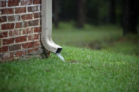 Working gutter on a brick house with flowing water into the grass during rain storm Standard-Bild