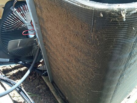 Dirty condenser coil fins on a home air conditioner compressor in need of cleaning and maintenance by technician.