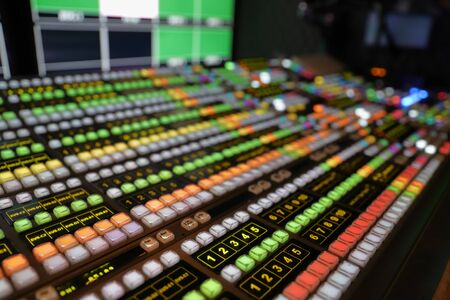 Broadcast Video Switcher used for live events and television production, with colorful lights and buttons