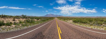 Panoramic view of a long straight road in the desert, leading to a beautiful mountain range under a blue sky with clouds