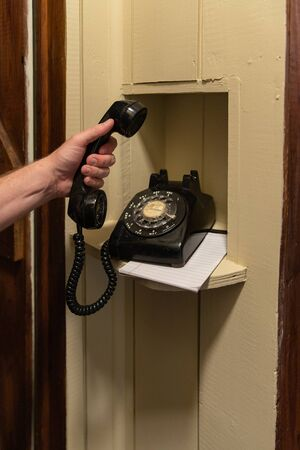 Hand holding handset of old black rotary phone in hallway phone nook