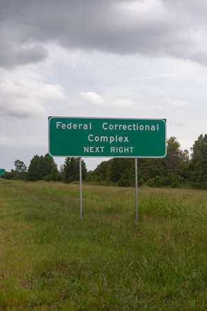 Federal Correctional Facility sign on the side of highway