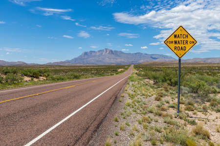 """""""Watch for water on Road"""" sign along a long straight road in the desert, leading to a beautiful mountain range under a blue sky with clouds"""