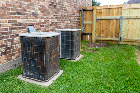 Two older HVAC air conditioner systems next to brick home with copy space.